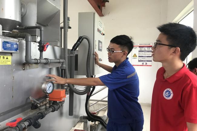 张心宇技术顾问为实践团成员讲解污水处理器的构造。